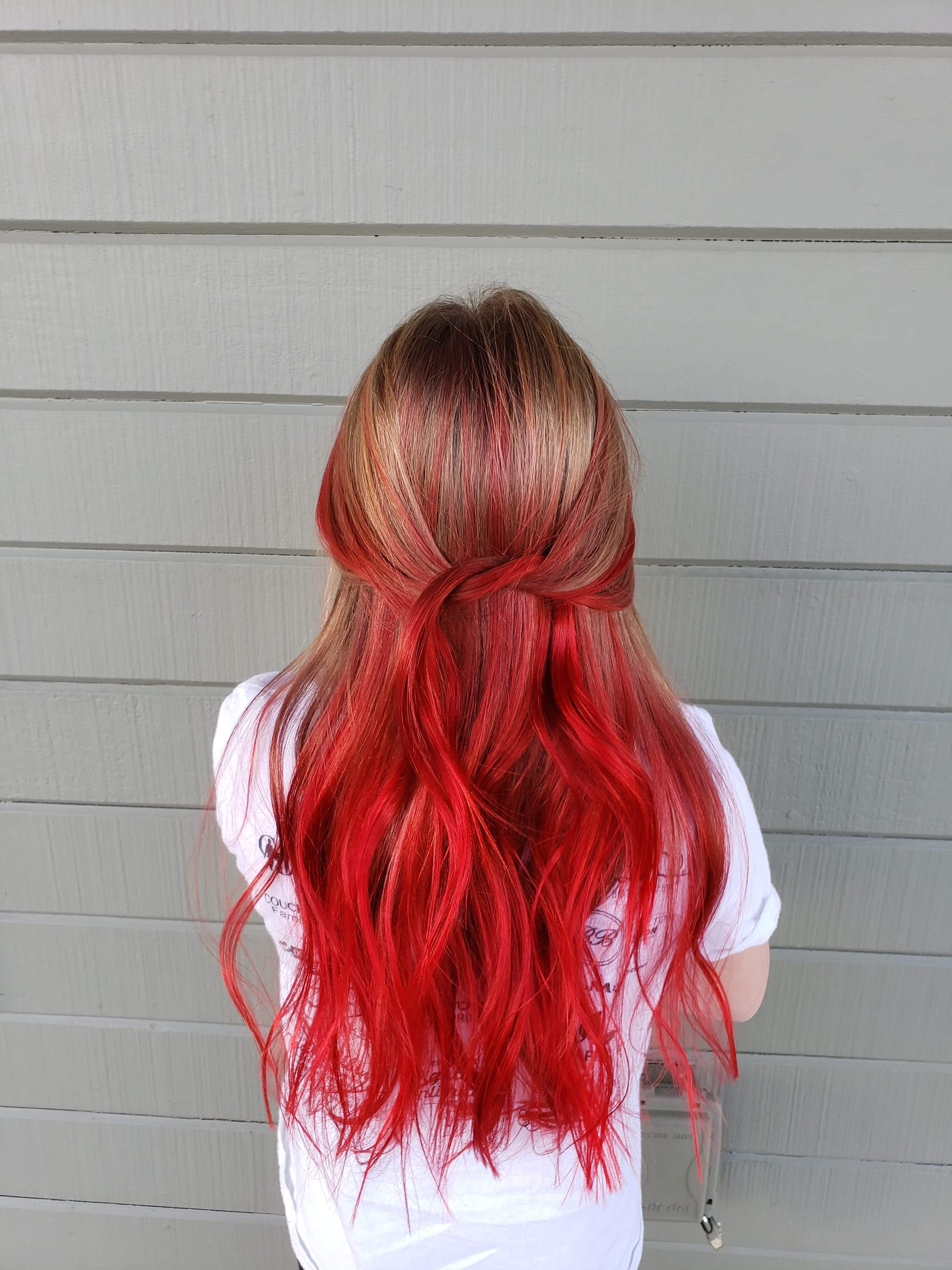 Woman with long blonde to red ombre hair over white shirt.