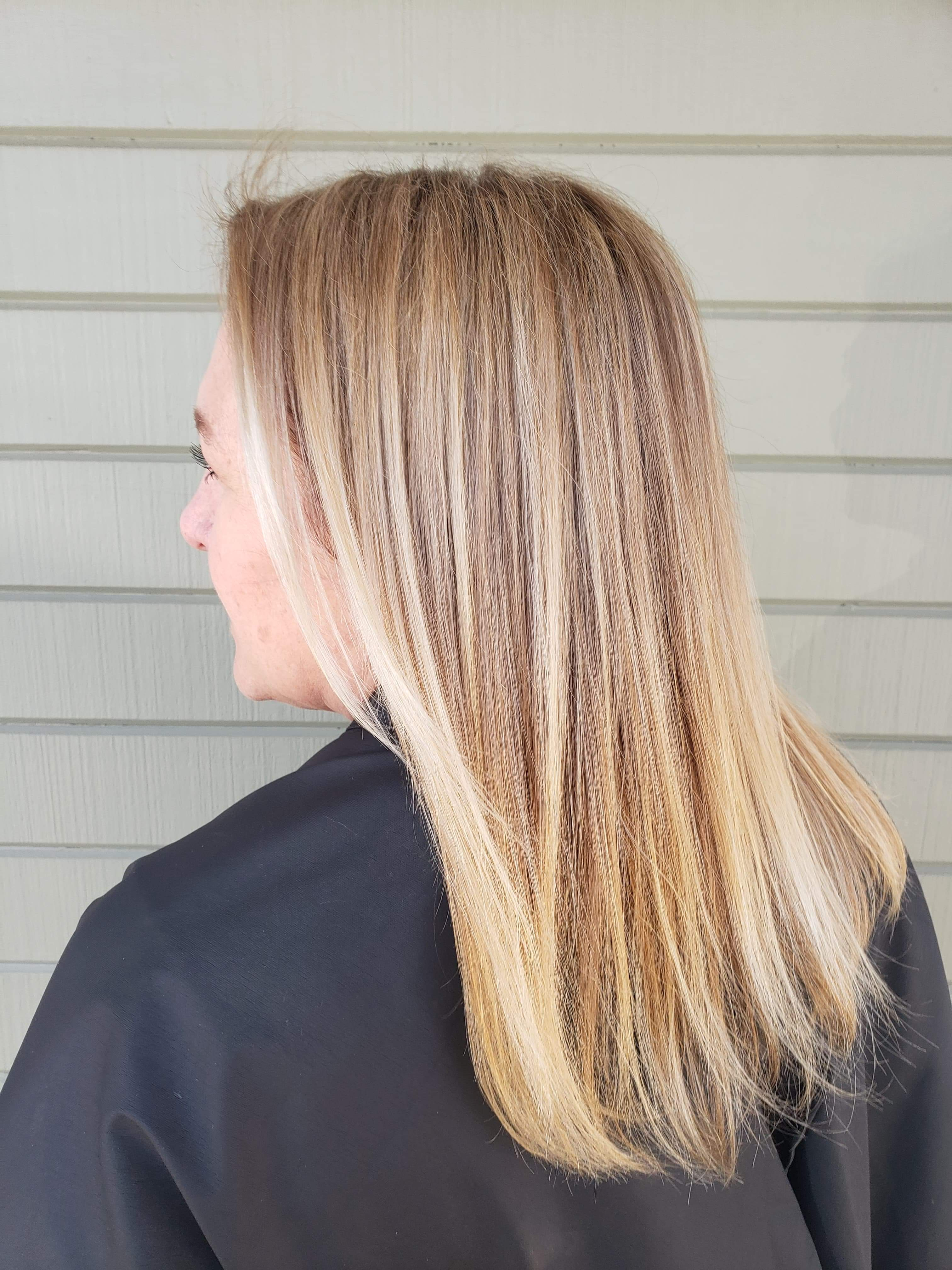 Side view of woman with medium-length blonde hair over black drape.